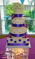 Celebrate your Wedding with an Beautiful White Wedding Cake with Dots and Purple Ribbon